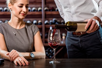 Sommelier pouring wine to the glass