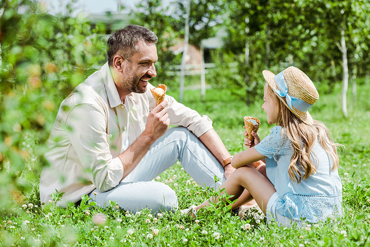 father and daughter eating ice cream on a farm
